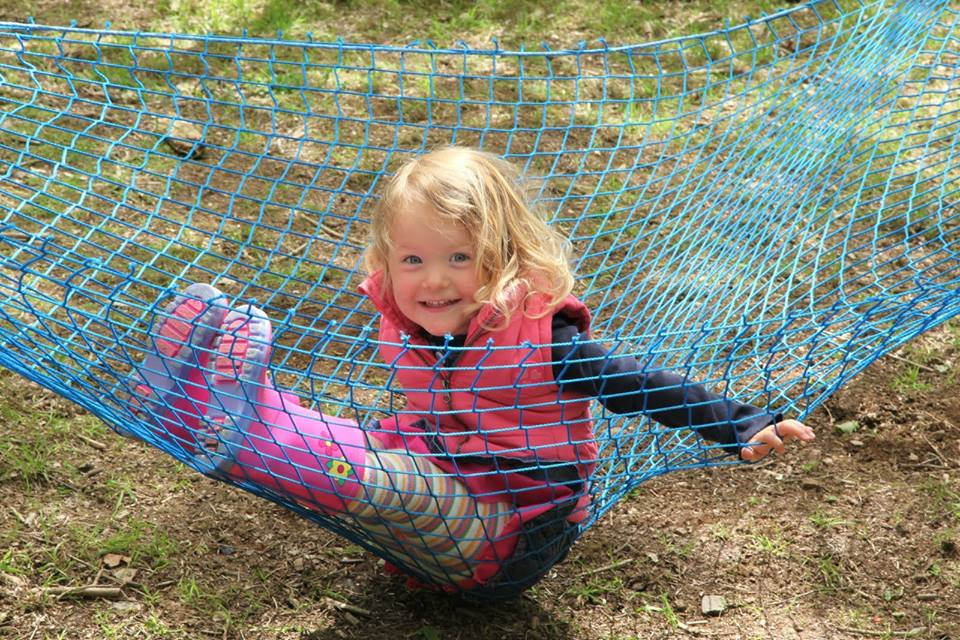 child at forest school in net