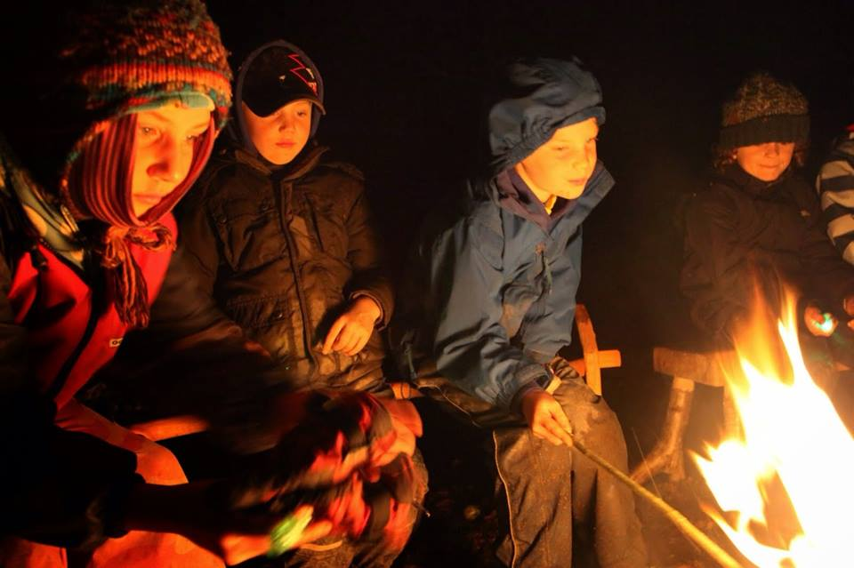 children around campfire in winter forest school