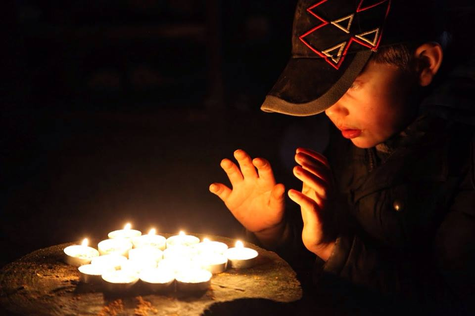 boy at forest school in winter with candles